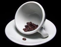 Kop koffiebonen op schotel stock afbeelding