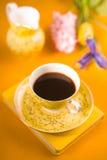 Kop met koffie, bloemen, notitieboekje op een gele achtergrond Royalty-vrije Stock Afbeeldingen