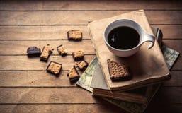 Kop met koffie en boeken, koekje op houten lijst Royalty-vrije Stock Foto's