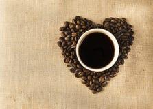 Kop met koffie en hart van koffie beanes Stock Afbeelding