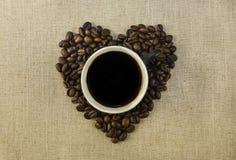 Kop met koffie en hart van koffie beanes Royalty-vrije Stock Afbeeldingen