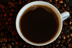 Kop met koffie op achtergrondkoffiebonen royalty-vrije stock afbeeldingen