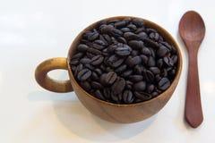 Kop met koffiebonen op witte achtergrond worden geïsoleerd die Royalty-vrije Stock Foto