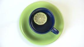 Kop met thee en plak van roterende citroen, hete drank stock footage