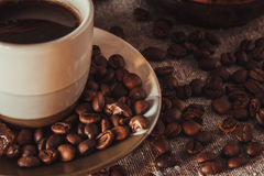 Kop op schotel met zich het verspreiden van koffiebonen en suiker stock foto's