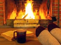 Kop thee, boek, de voeten van vrouwen in warme sokken op een houten lijst tegenover een brandende open haard royalty-vrije stock afbeeldingen