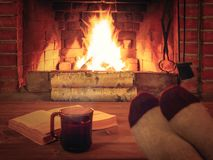 Kop thee, boek, de voeten van vrouwen in warme sokken op een houten lijst tegenover een brandende open haard royalty-vrije stock foto's