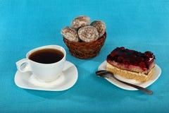 Kop thee, cake en peperkoek op blauwe achtergrond Stock Afbeeldingen