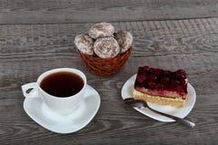 Kop thee, cake en peperkoek op houten achtergrond Stock Afbeeldingen