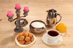 Kop thee, citroen, bakkerij, suikerkom, theepot en kandelaar Stock Foto's