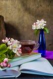 Kop thee dichtbij boeken en bloesemtakken van appelboom royalty-vrije stock afbeelding