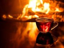 Kop thee door de open haard stock foto