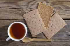 Kop thee en bruin kernachtig brood stock fotografie