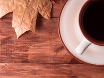 Kop thee en esdoornbladeren op de achtergrond op houten Hoogste mening Royalty-vrije Stock Fotografie