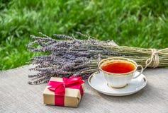 Kop thee en giftdoos Thee in de verse lucht Nuttige thee met kruiden Stock Fotografie