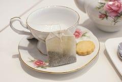 Kop thee en koekje met tradtionaltheestel stock afbeelding