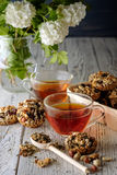 Kop thee en koekjes van noten en rozijnen wordt gemaakt die Stock Afbeeldingen