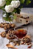 Kop thee en koekjes van noten en rozijnen wordt gemaakt die Stock Fotografie