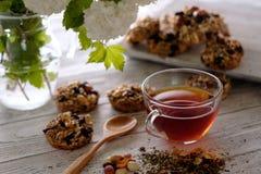 Kop thee en koekjes van noten en rozijnen wordt gemaakt die Stock Foto's