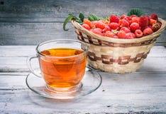Kop thee en mand met framboos Stock Foto's