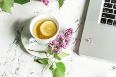 Kop thee en seringen naast de computer Royalty-vrije Stock Foto