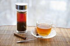 Kop thee en theeblaadjes bij een venster Stock Foto