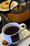 Kop thee en theepot en cake op een zwarte achtergrond Stock Foto's