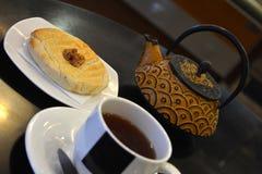 Kop thee en theepot en cake op een zwarte achtergrond Stock Afbeelding