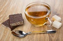Kop thee, lepel, klonterige suiker, theelepeltje en gebroken wafeltje stock afbeelding