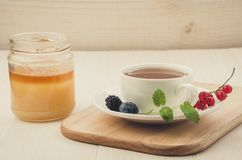 Kop thee met bessen en munt in een schotel en honingskop thee met bessen en munt in een schotel en honing op een houten dienblad stock fotografie