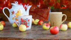 Kop thee met de herfstbladeren en appelen op houten lijst stock video