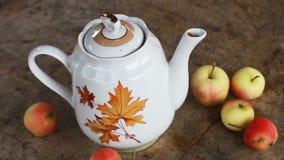 Kop thee met de herfstbladeren en appelen op houten lijst stock footage
