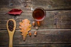 Kop thee met de herfstbladeren op houten achtergrond royalty-vrije stock fotografie