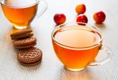 Kop thee met koekjes en pruim Stock Fotografie