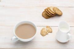 Kop thee met melk en sesamkoekjes Royalty-vrije Stock Afbeelding