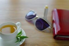 Kop thee met munt op een lijst Stock Afbeelding