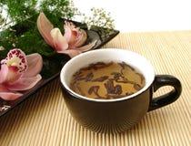 Kop thee met roze orchideeën op zwarte plaat over mat stro Royalty-vrije Stock Afbeelding