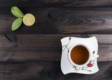 Kop thee met verse kalk op houten lijst Stock Fotografie