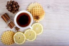 Kop thee met wafels en kaneel, badian citroen, pinecone royalty-vrije stock afbeelding