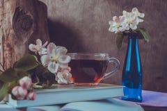 Kop thee op boek met bloemen stock foto's