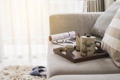 Kop thee op houten dienblad op bank in woonkamer Stock Afbeeldingen