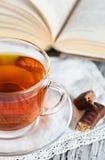 Kop thee, suikergoed en boek stock fotografie