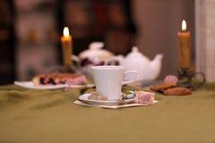 Kop thee tegen een achtergrond van kaarsen en pastei Stock Foto's