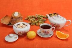 Kop thee, theepot, bakkerij, suikerkom, citroen, oranje plak Stock Foto's