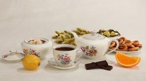 Kop thee, theepot, suikerkom, citroen, oranje plak, chocolade Stock Foto's