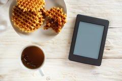 Kop thee, wafel en ebook Stock Foto
