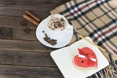 Kop van cappuccino, het hart gestalte gegeven bericht van de koekjesbreedte, notitieboekje en geruite plaid op een bruine houten  royalty-vrije stock afbeeldingen