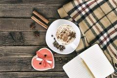 Kop van cappuccino, het hart gestalte gegeven bericht van de koekjesbreedte, notitieboekje en geruite plaid op een bruine houten  stock afbeeldingen