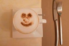 Kop van cappuccino met een glimlach van kaneel op een witte schotel en beige tafelkleden Stock Afbeelding