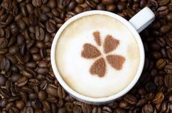 Kop van cappuccino met kaneelpatroon op een achtergrond van coffe Stock Foto